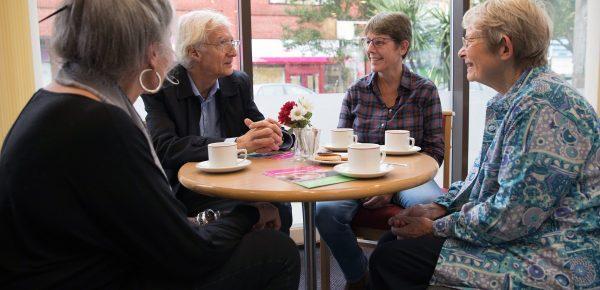 People sat round table having coffee