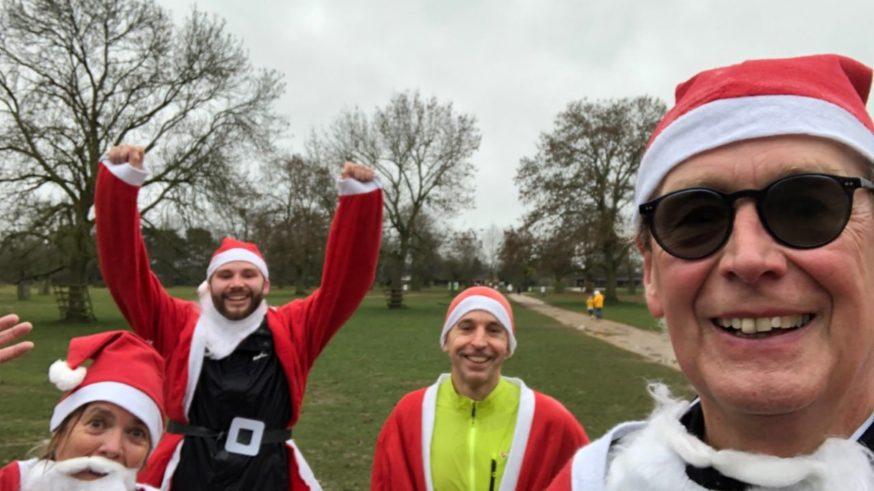 Smiling people dressed as Santa